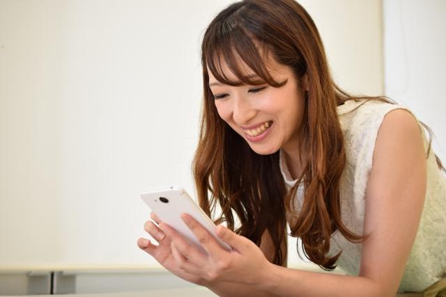 携帯で笑顔の女性